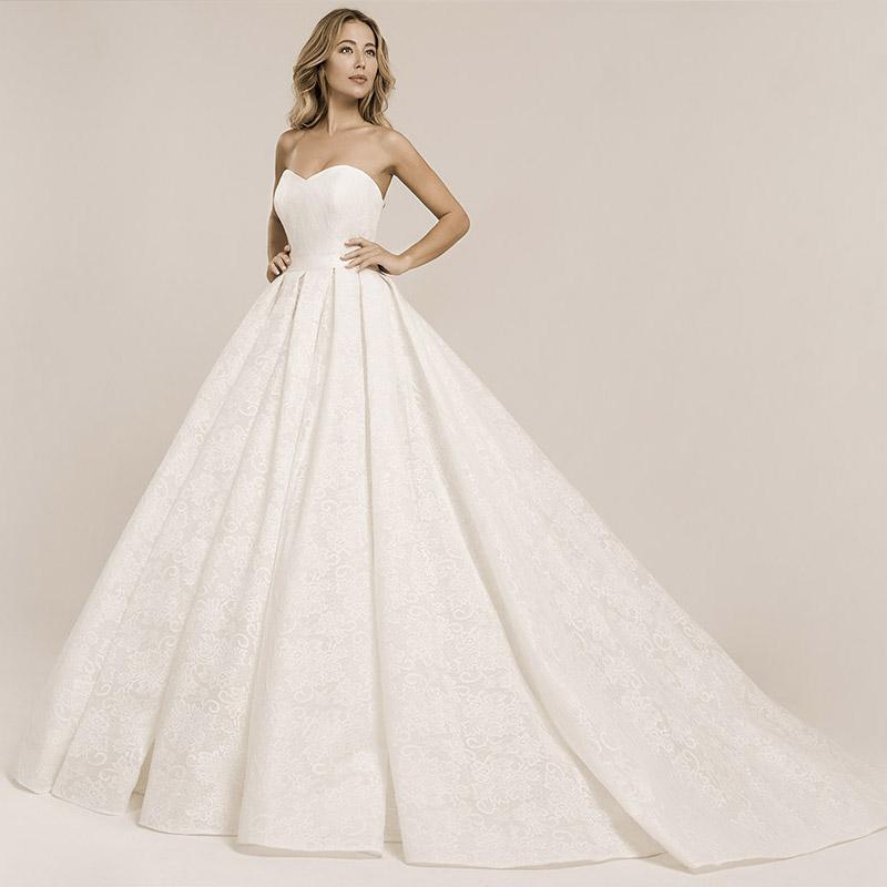 Frau trägt ein Prinzessinnen Brautkleid mit einer durchgängigen Spitzenapplikation