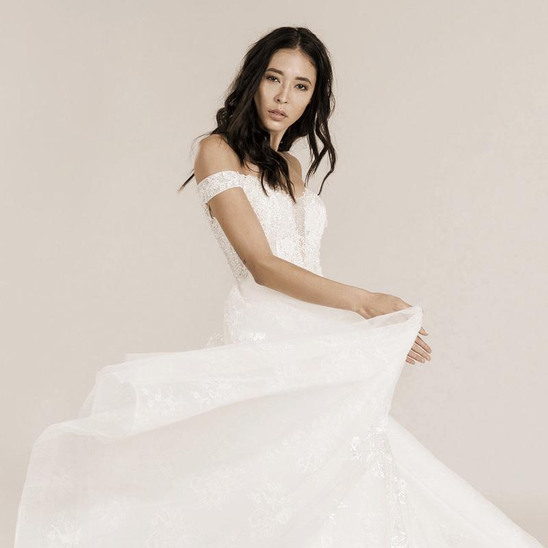 Frau schwingt die Schleppe. Das Brautkleid hat Off-Shoulder.