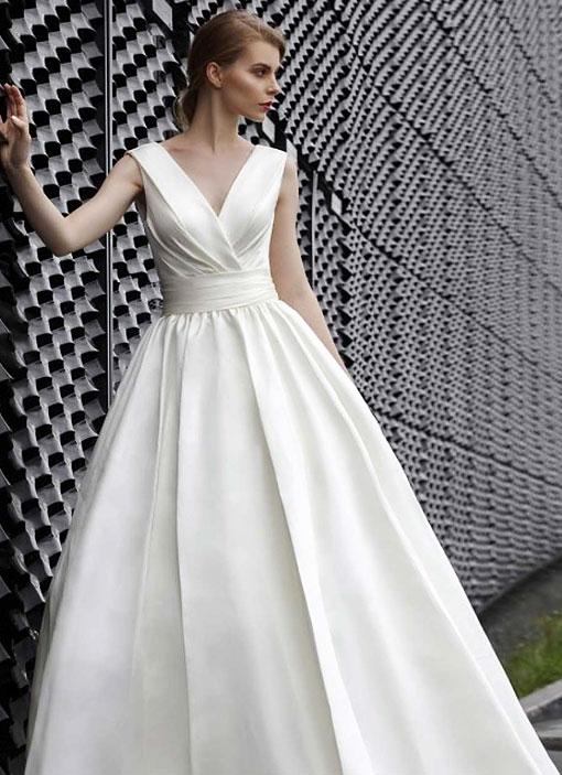 Frau trägt ein Hochzeitskleid aus Mikado Satin mit einem raffinierten Oberteil und einer Blumenapplikation am Rücken