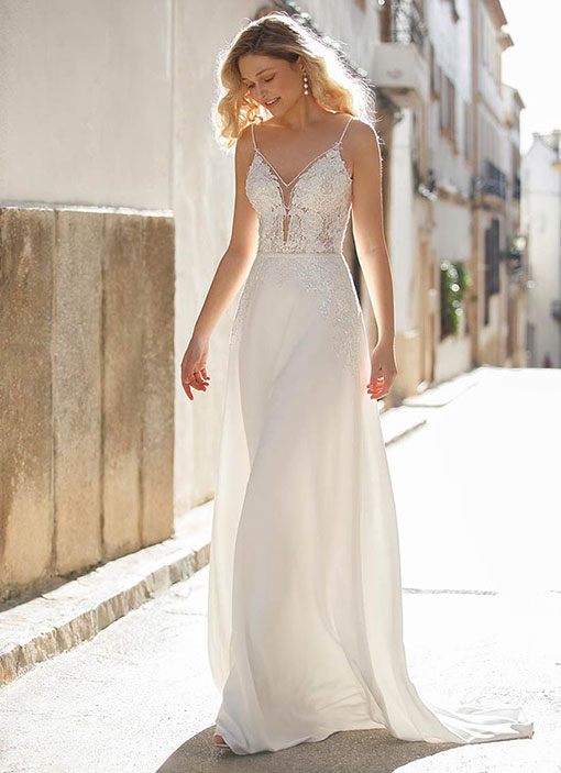 Frau präsentiert ein enges Brautkleid mit einem Chiffonrock und einem transparenten Spitzenoberteil