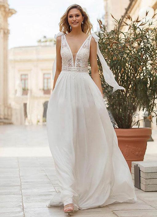 Frau trägt ein Chiffon Brautkleid mit einem Spitzenobert und Flatterärmel