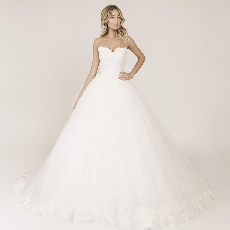 Frau trägt ein Prinzessinnen Hochzeitskleid mit einer Spitzenkorsage und einem Tüllrock mit Spitze am Saum