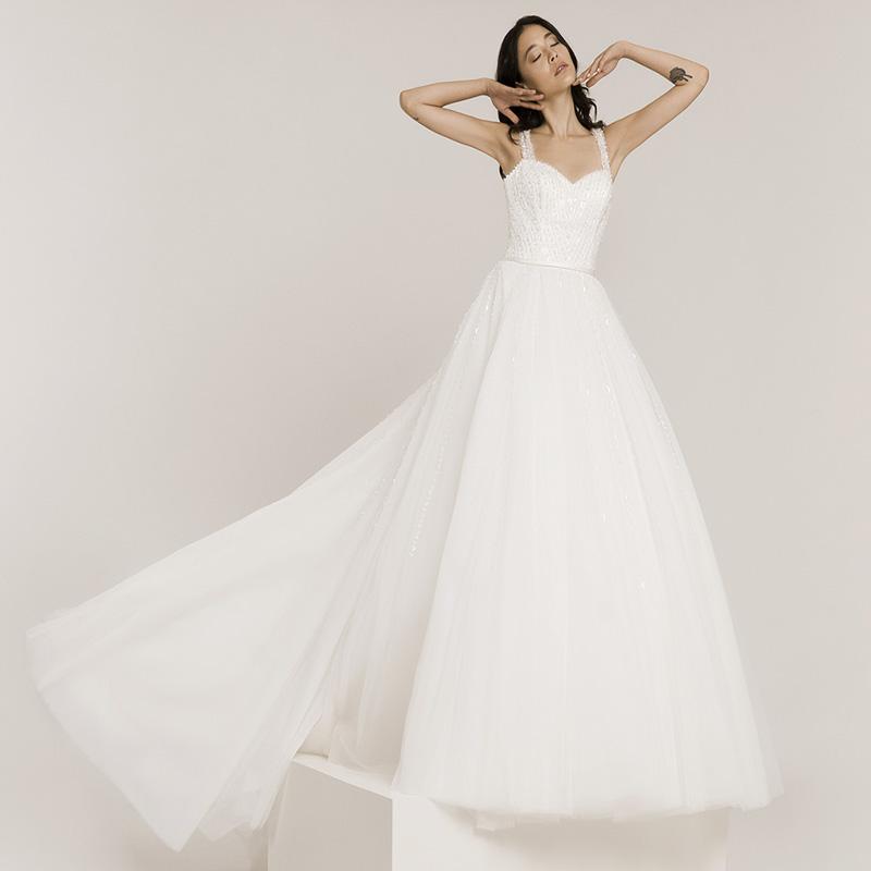 Frau trägt Brautkleid mit vielen Glitzerelementen. Das Brautkleid hat Träger und einen weiten Tüllrock.