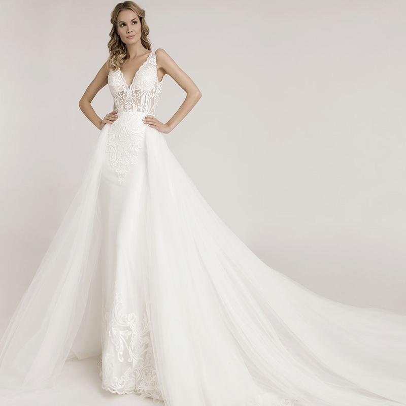 Frau auf dem Bild präsentiert ein eng anliegendes Brautkleid mit Spitzenapplikationen, darüber trägt sie eine abnehmbare Schleppe