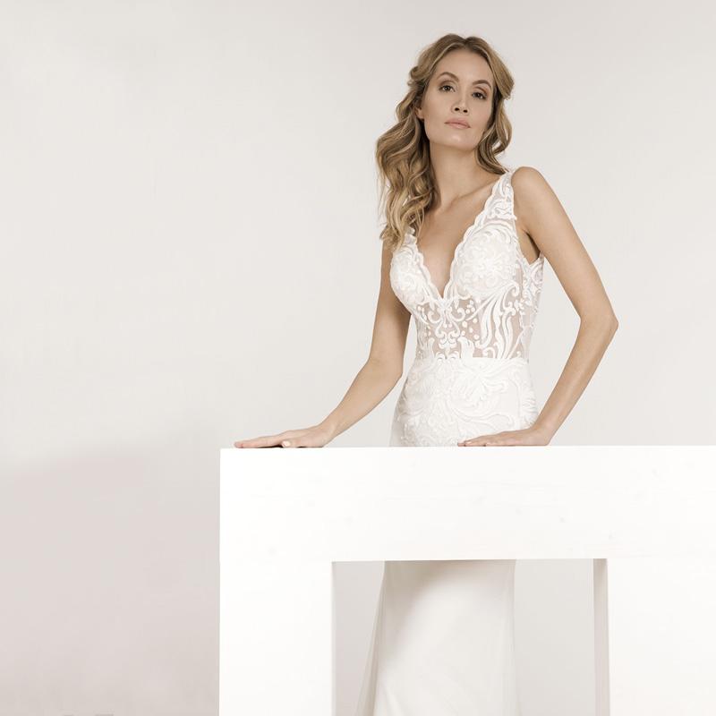 Frau auf dem Bild trägt ein enges Hochzeitskleid mit einem Spitzenoberteil und V-Ausschnitt