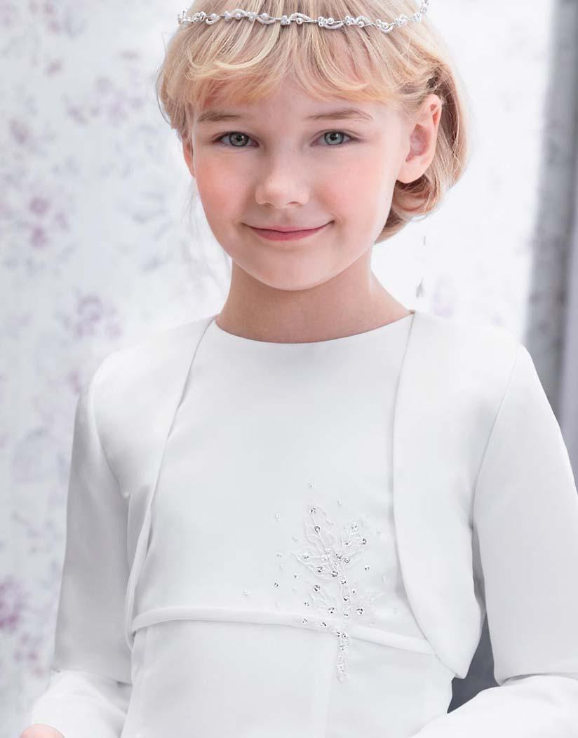 Mädchen trägt ein weisses Kinderbolero und ein Kommunionkleid verziert mit Strasssteinen