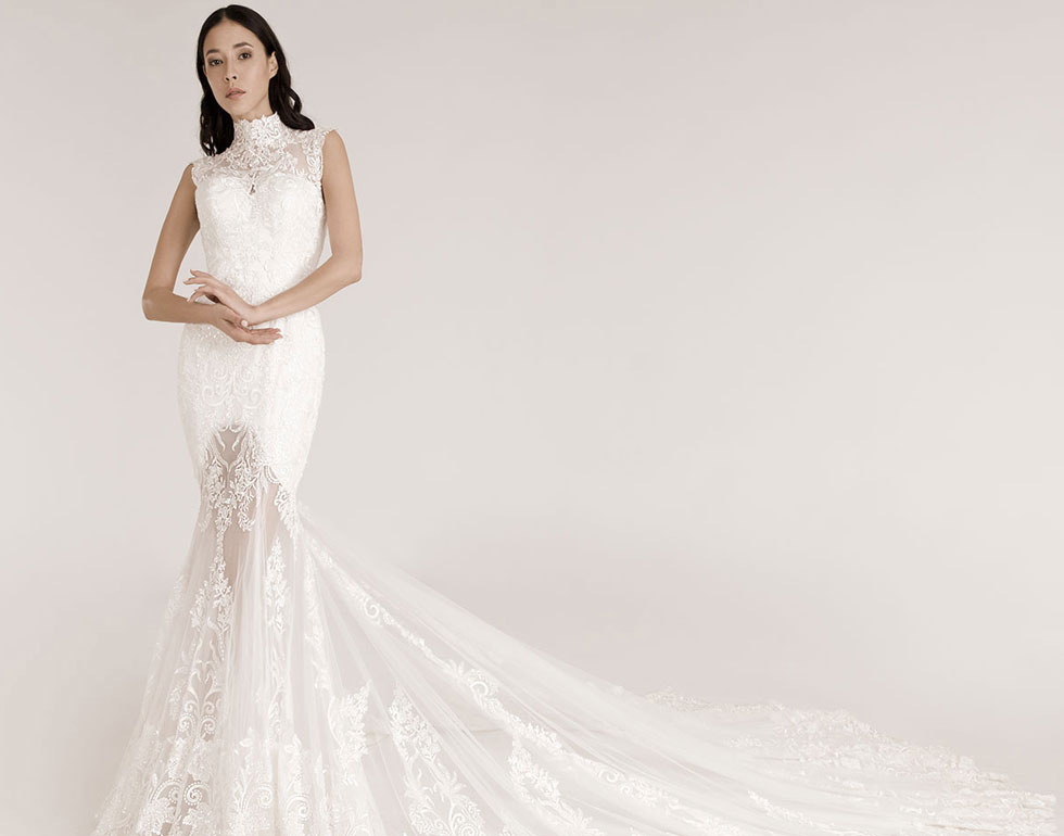 Model trägt ein eng anliegendes Brautkleid mit Stehkragen und Spitze