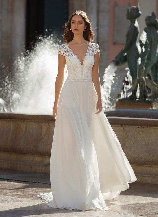 Frau auf dem Bild trägt ein schlichtes Brautkleid mit Chiffonrock und einem Spitzenoberteil mit Schulterärmel