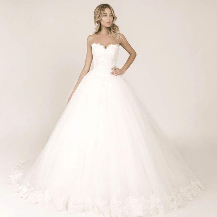 Frau präsentiert ein Prinzessinnen Brautkleid mit Spitzenkorsage und einem weiten Tüllrock