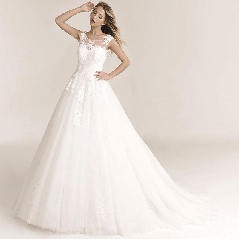 Frau trägt ein A-Linie Hochzeitskleid mit Tattoospitze und einem weiten Tüllrock