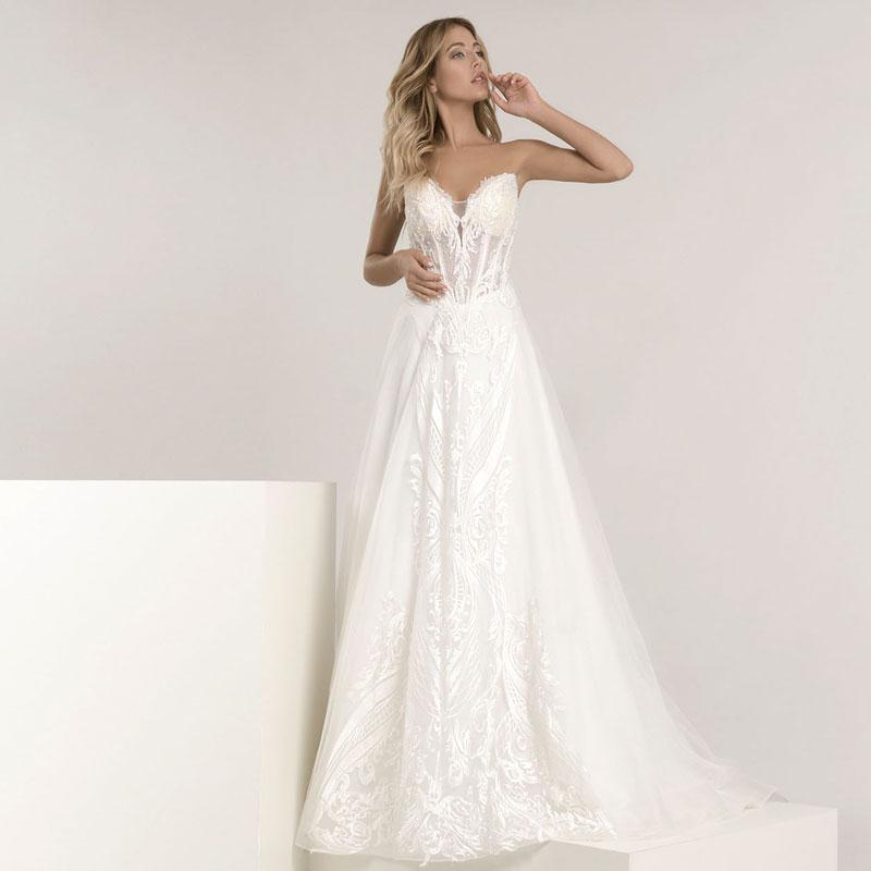 Model trägt ein extravagantes Kleid mit einer abnehmbaren Schleppe