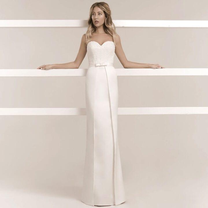 Frau trägt ein schmales Hochzeitskleid aus Satin mit einer Spitzenkorsage