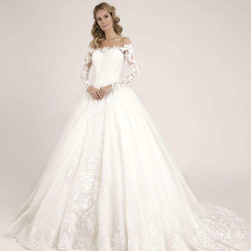 Frau präsentiert ein Prinzessinnen Hochzeitskleid mit Carmenträgern