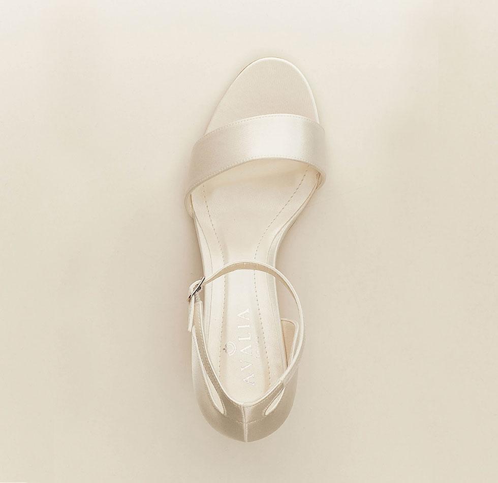 Auf dem Bild sind Brautschuhe zu sehen mit einem Riemen, vorne offen und einem kleinen Absatz in ivory