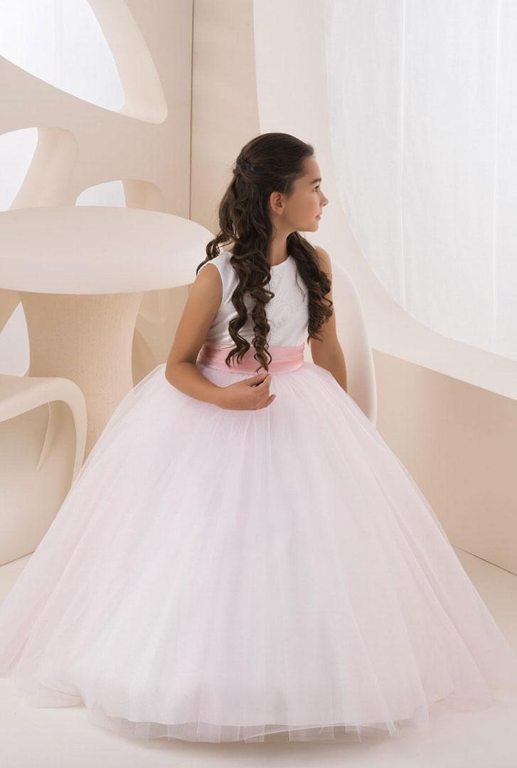 Mädchen trägt ein Blumenmädchenkleid mit einem weiten langen Tüllrock mit einem Spitzenoberteil in ivory und pink