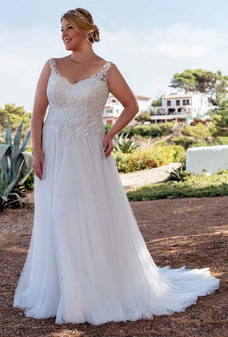 Frau trägt schlichtes Plus Size Hochzeitskleid mit Spitzenoberteil